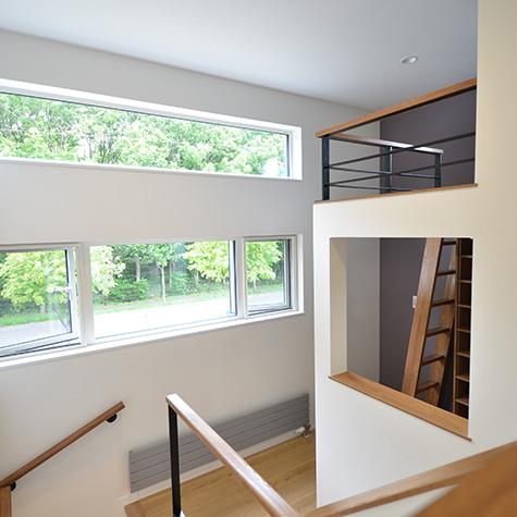 中二階に防風林を望む書斎のある家